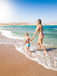 Beautiful young mother holding her little son by hand and walking on the sandy sea beach at bright sunny day. Child relaxing and having good time during summer holiday vacation.