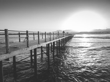 Black And White Image Of Sun Setting Down Over The Ocean Waves And Long Wooden Pier