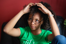 Portrait Of A Pretty Teenager As She Combs Her Kinky Curly Mixed Race Hair
