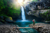 Travel photographer with backpack and camera in hand make epic photo amazing waterfall in the sun rays on background nature landscape