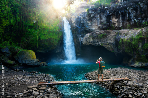 Door stickers Black Travel photographer with backpack and camera in hand make epic photo amazing waterfall in the sun rays on background nature landscape