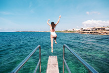 Woman Jumping Off A Springboard