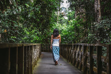 Beautiful Woman With Blue Skirt Walking Along A Wooden Path Through The Rainforest