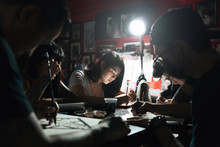 Group Of Professionals Tottooers Designing Tattoos In Studio