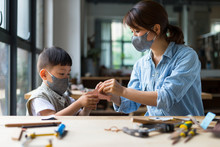 Carpenter Wearing Mask Working With Her Son In Workshop