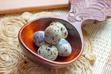 Fresh Raw Quail Eggs In Wooden Spoon On Rustic Straw And Wooden Vintage Background