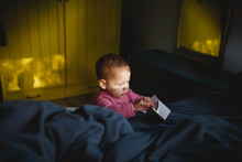 A Baby Girl Playing With An Empty Carton Box On Bed
