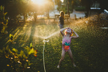 Girl In Swimsuit Playing On Grass With Sprinkler