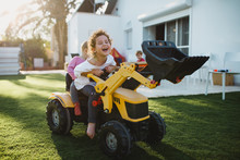 Smiling Girl With Her Sister Sitting On Toy Tractor In Yard