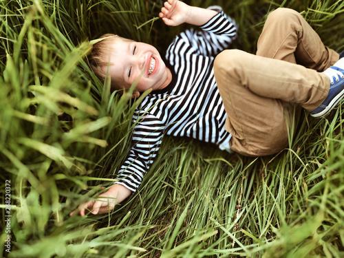 Smiling boy lying on green grass - 268220372
