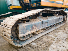 Closeup Image Of Excavator Tracks Covered In Dirt On The Construction Site