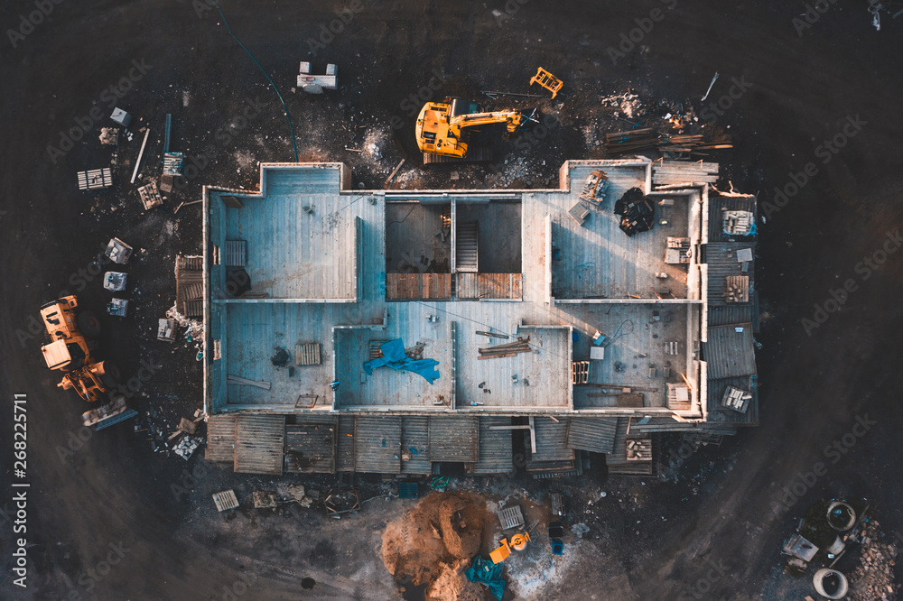 Fototapeta Aerial birds eye image of the frame of a house being built on a construction site at sunset - Wooden floor and walls are visible
