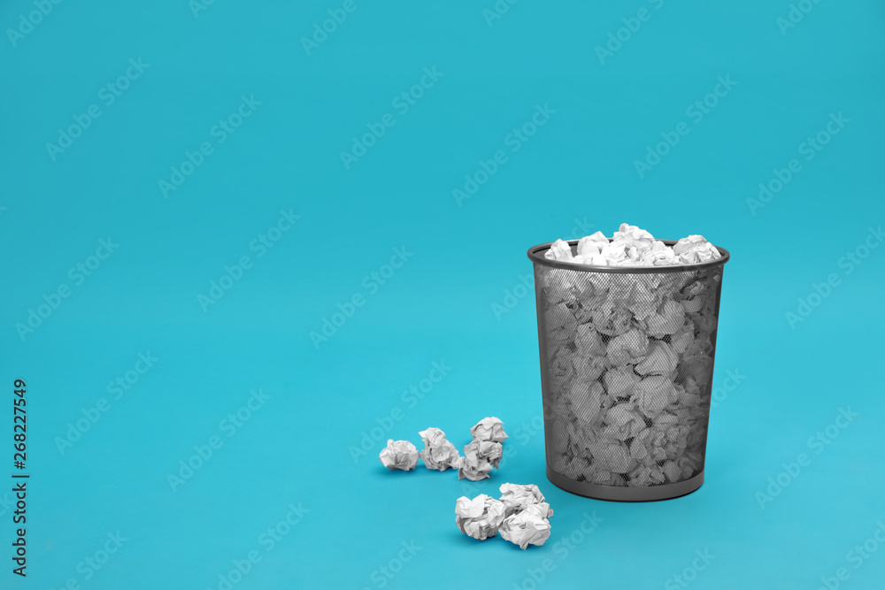 Metal bin with crumpled paper on color background, space for text