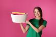 Leinwandbild Motiv Happy young woman holding basket with laundry on color background
