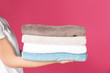 Leinwandbild Motiv Young woman holding clean towels on color background, closeup. Laundry day