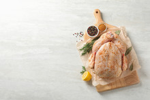 Board With Raw Spiced Turkey And Ingredients On Light Background, Top View. Space For Text
