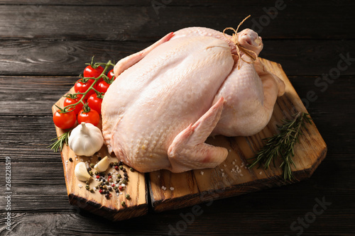 Board with raw turkey and ingredients on wooden background Canvas