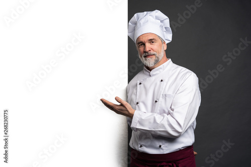 Fototapeta Portrait of a happy mature chef cook showing copyspace on the palms isolated on black background. obraz