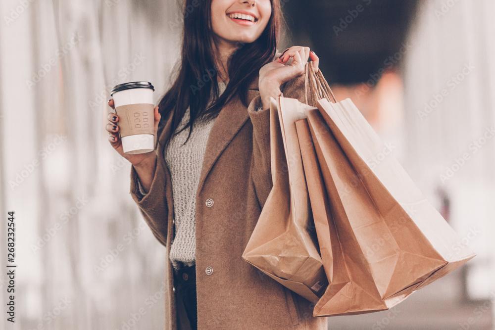 Fototapeta Beautiful fashionable woman with shopping bags and coffee walking near mall.