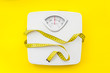 canvas print picture - bathroom scales and measuring tape for weight loss concept on yellow background top view