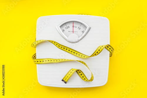 bathroom scales and measuring tape for weight loss concept on yellow background Canvas Print