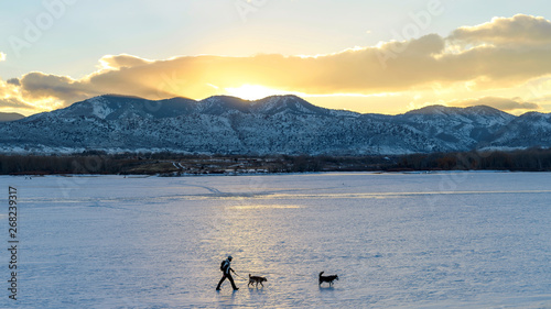 Fotografie, Tablou  Hiking on Frozen Mountain Lake - A hiker, with two dogs, walking on snow-covered frozen Bear Creek Lake on a cold winter evening