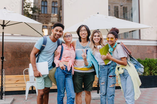 Fototapety, obrazy: Laughing asian boy in glasses and shorts embracing charming blonde girls in front of outdoor cafe. Joyful students came to open-air restaurant to celebrate end of exams