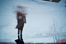 Blurry Reflection In A Puddle Of Alone Walking Person On Wet City Street During Rain And Snow. Mood Concept