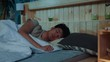 Close up young asian man sleeping in bed bedroom something dreams home comfortable morning wake up guy relax good active lazy pillows night portrait slow motion