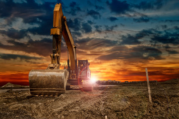Excavating machinery at the construction site, sunset in background.