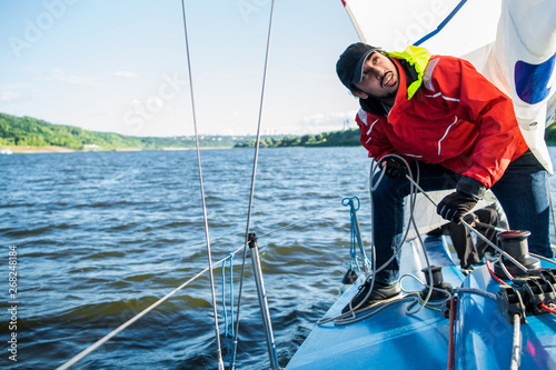 Sailor man at boat bow with cap looking away the sea while sailing