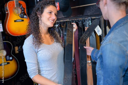 Poster de jardin Magasin de musique shop assistant showing guitar to customer