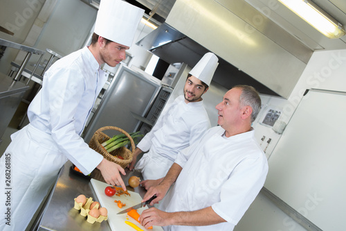 Cadres-photo bureau Pain professional chef and his trainees cooking fresh vegetable salad