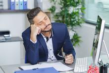 Businessman Dozing At His Desk