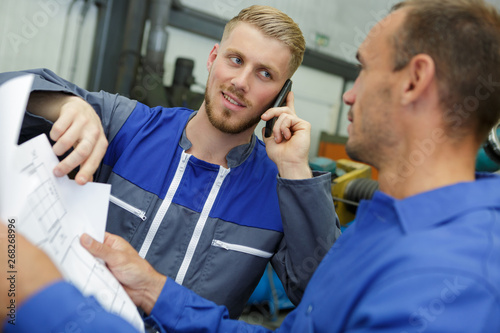 two businessmen with plan walking in factory shop floor Canvas Print
