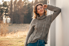 Outdoor Fashion Photo Of Young Beautiful Woman In  Brown Knitting Sweater And Jeans In Autumn Field  Landscape. Fashion Lookbook.