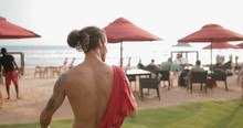 A Young Sports Guy Without A Shirt Goes To The Beach In The Evening. Tracking Shot. In Slow Motion. Shot On Canon 1DX Mark2 4K Camera