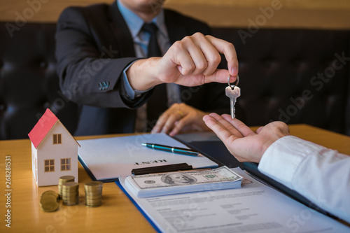 Cuadros en Lienzo  Salesman house brokers provide key to new homeowners in office.