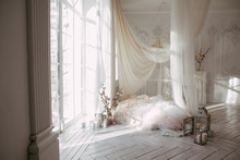 A Large Clean Bright Room With A Window Of White Wooden Floor, A Mattress-bed, Decorated With Tulips Curtains Canopies, Vases With Cotton Branches