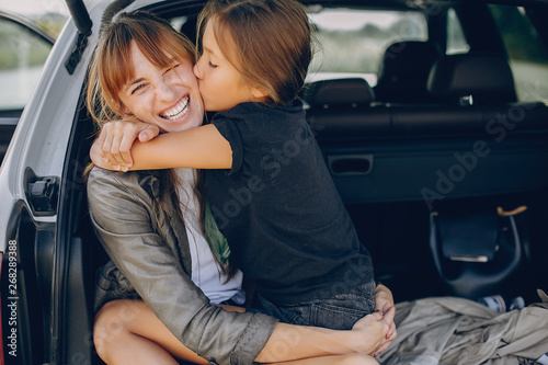 Fototapeta Fashionable mother with daughter. Family is sitting in the trunk. Girl in a black t-shirt obraz