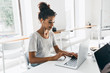 Romantic african girl with trendy hairstyle sitting at her workplace and analysing data. Indoor portrait of black female student working with laptop before exam.
