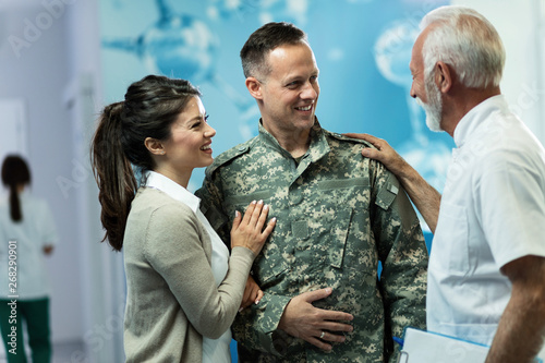 Fotografía  Happy military officer and his wife talking to a doctor in a hallway at clinic