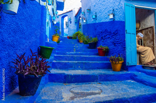Deurstickers CHEFCHAOUEN, MOROCCO, 20 AUGUST 2018: Old man resting in the stairs of the blue town