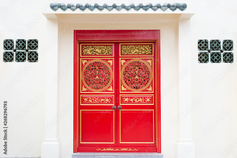 Asia entrance architecture..Chinese twin wooden doors in red and golden color on white wall.