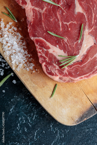 Fotografie, Obraz  Uncooked beef steak on wooden board with rosemary and sea salt.