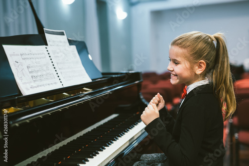 Billede på lærred happy little girl teaching to play piano in music school