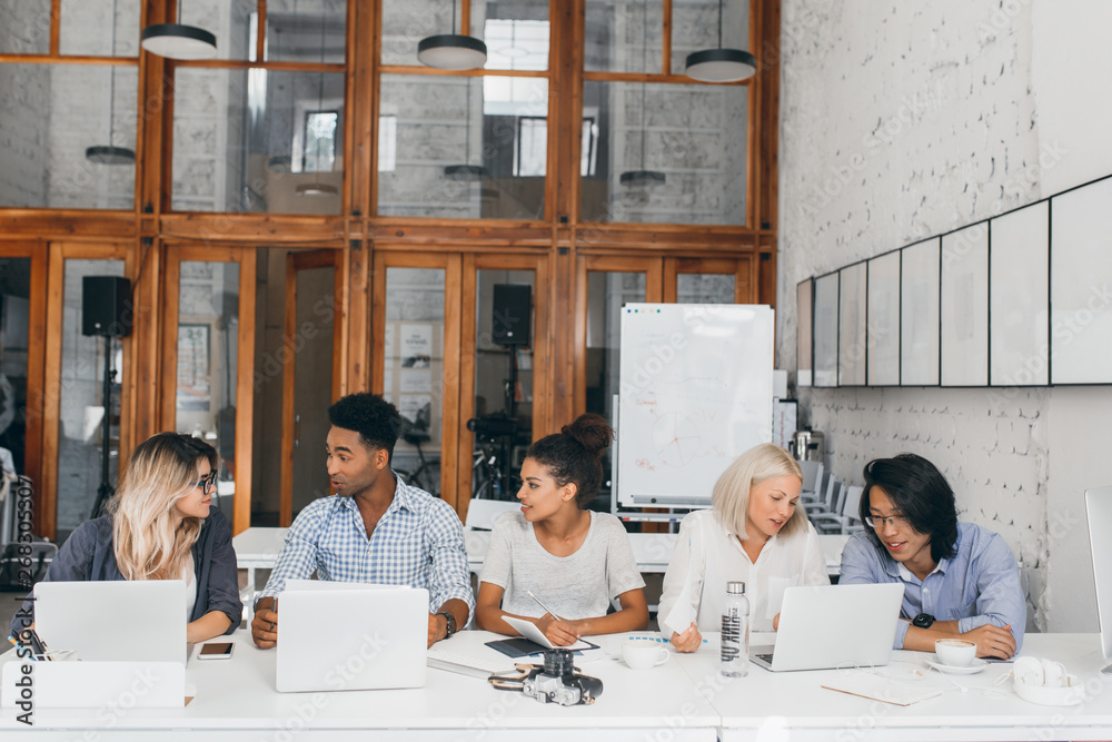 Fototapety, obrazy: Blonde girl in white shirt talking with asian friend and drinking coffee near laptop with flipchart on background. Freelance web-designers working together in conference hall and using computers.