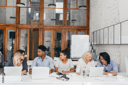 Valokuva  Blonde girl in white shirt talking with asian friend and drinking coffee near laptop with flipchart on background