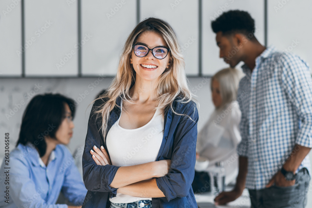 Fototapeta Confident blonde female manager posing with smile after conference with other employees. Asian programmer talking with african freelancer while fair-haired secretary laughing on foreground.