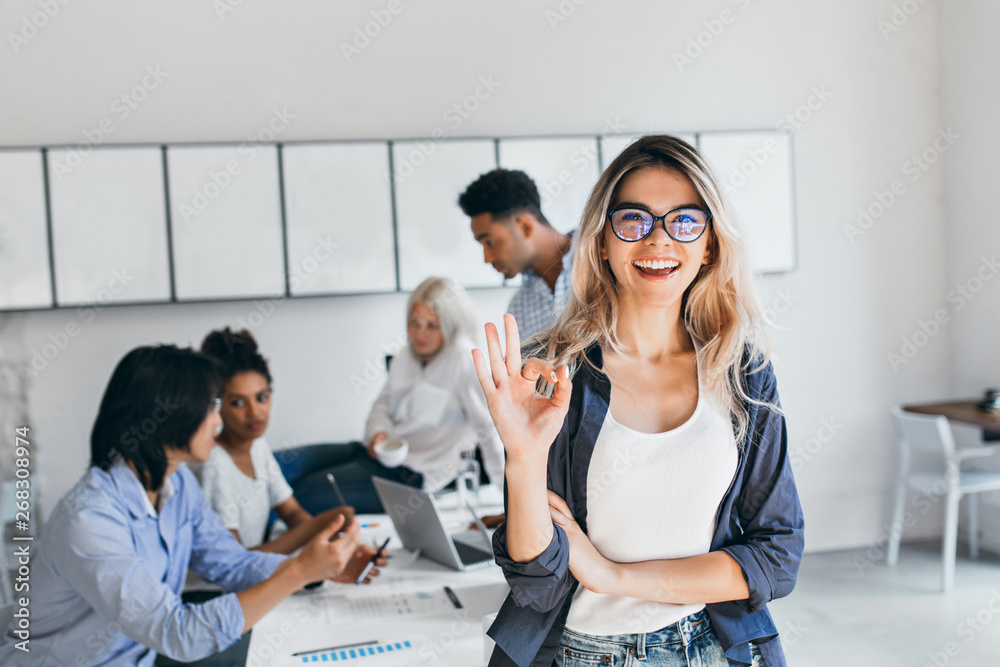 Fototapeta African students with serious face expression preparing for seminar while blonde girl posing with okay sign. Young female businesswoman having fun in office after brainstorm with colleagues.